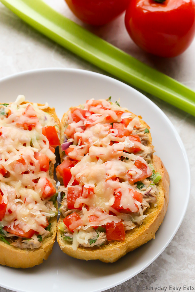 Close-up overhead view of Tuna Melts in a white plate with celery and tomatoes in the background.