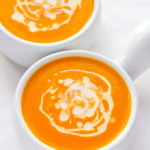 Overhead view of two bowls Creamy Carrot Ginger Soup on a white background.
