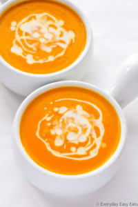 Overhead view of two bowls of Coconut Carrot Soup on a white background.