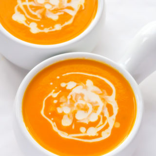 Overhead view of two bowls Carrot Ginger Coconut Soup on a white background.