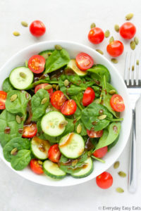 Overhead view of Cherry Tomato Spinach Salad in a white bowl against a light background.