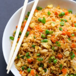 Close-up overhead view of Chinese Fried Rice in a white plate on a dark background.