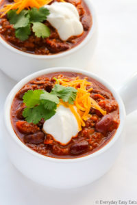Overhead view of two bowls of Ground Beef Chili, garnished with shredded cheese, cilantro and sour cream, on a white surface.