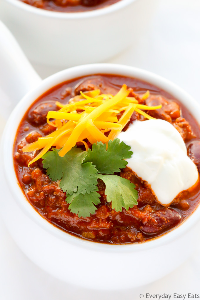 Close-up overhead view of a bowl of Ground Beef Chili, garnished with shredded cheese, cilantro and sour cream, on a white surface.
