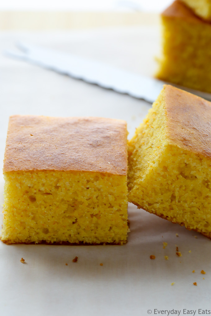 Close-up side view of sliced Buttermilk Cornbread on a wooden chopping board.