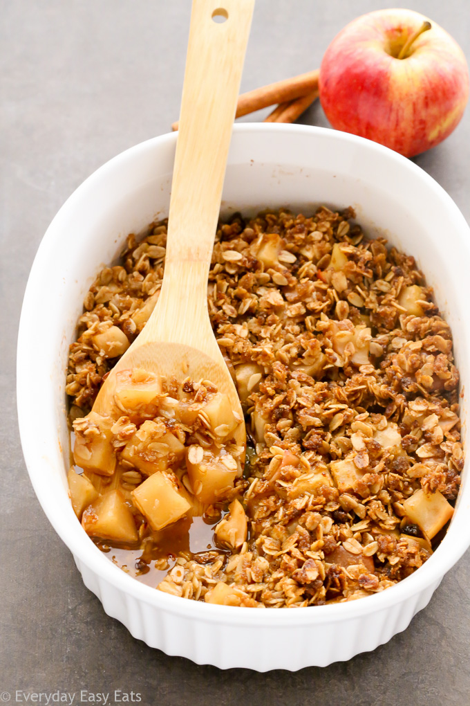 Overhead view of Healthy Apple Crisp in a large white serving dish with a wooden spoon taking a spoonful out.