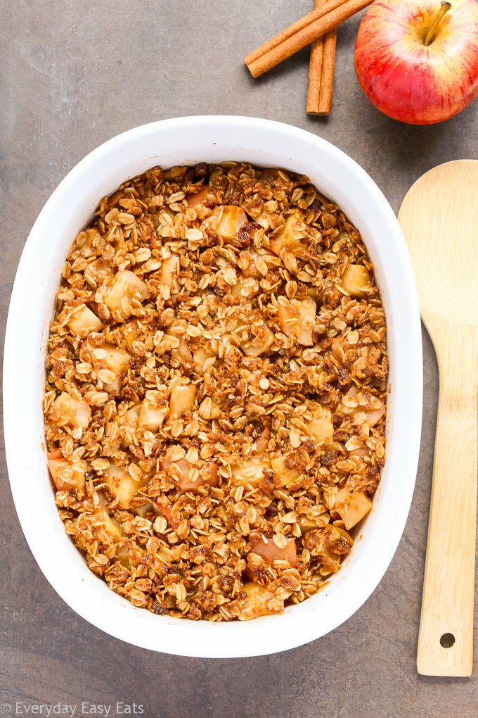 Overhead view of Healthy Apple Crisp in a large white serving dish with a wooden spoon beside of the dish.