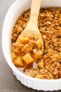 Close-up overhead view of Gluten-Free Apple Crisp in a large white serving dish with a wooden spoon taking a spoonful out.