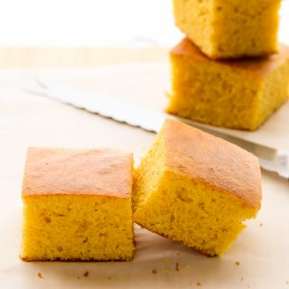 Side view of sliced Buttermilk Cornbread on a wooden chopping board.