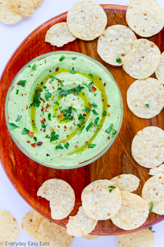 Close-up overhead view of a bowl of Healthy Avocado Dip on a wooden background with scattered tortilla chips.