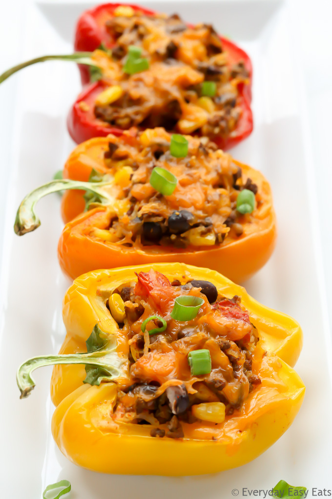 Overhead view of three Mexican Stuffed Peppers in a white serving dish.