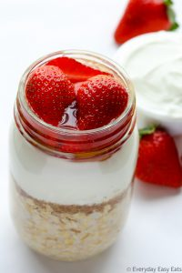 Overhead view of Strawberry Overnight Oats with Yogurt in a mason jar on a white background.