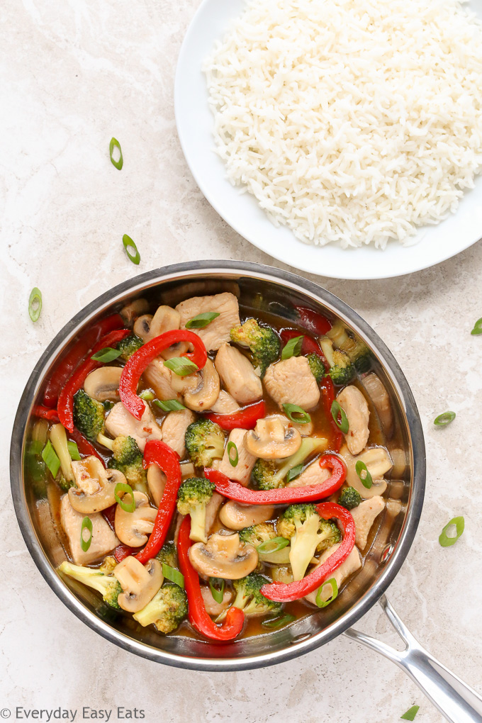 Overhead view of Chicken and Vegetable Stir-Fry in a wok with a plate of white rice beside it.