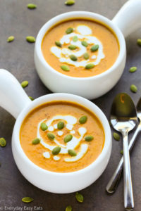 Curried Coconut Pumpkin Soup in white bowls with spoons on black background