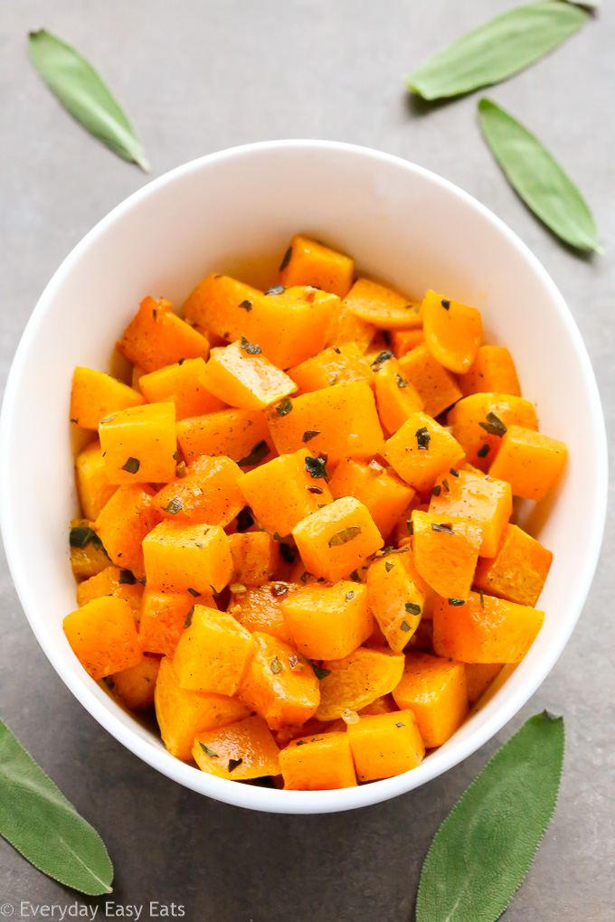 Overhead view of a serving bowl of Roasted Butternut Squash with Sage on a grey background.