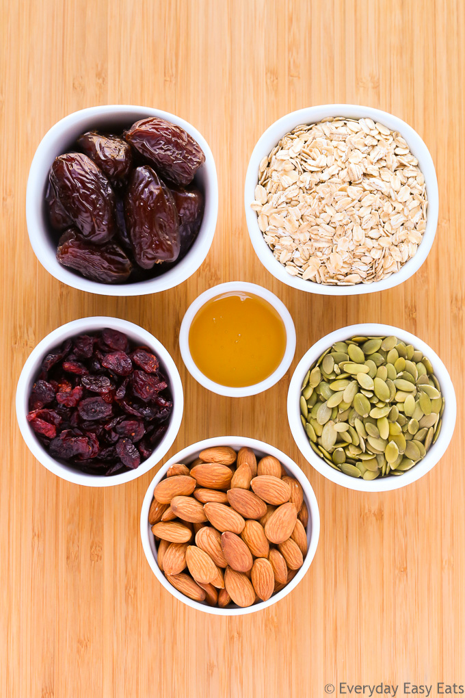 Overhead view of No-Bake Healthy Fruit and Nut Granola Bars ingredients in white bowls on a wooden background.