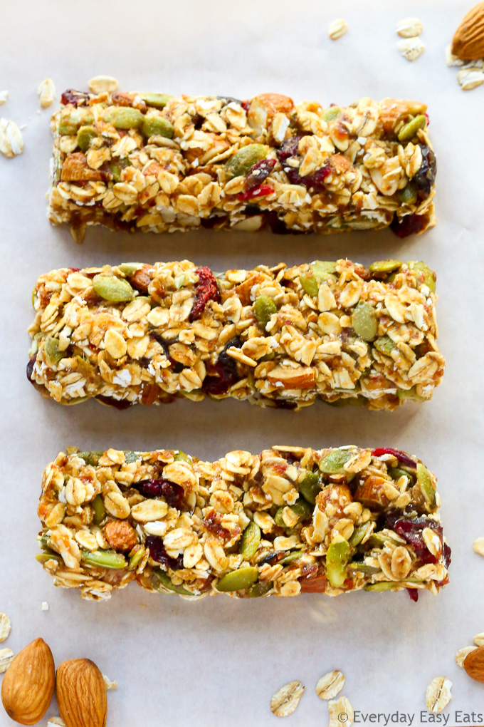 Close-up overhead view of three No-Bake Healthy Fruit and Nut Granola Bars on a white background.