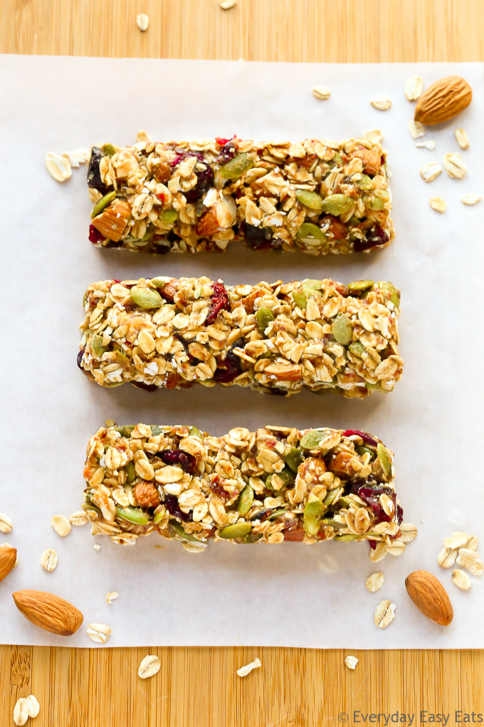 Overhead view of three No-Bake Healthy Fruit and Nut Granola Bars on a wooden background.