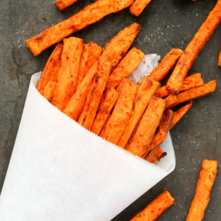 Overhead view of Spicy Baked Sweet Potato Fries against a dark background.
