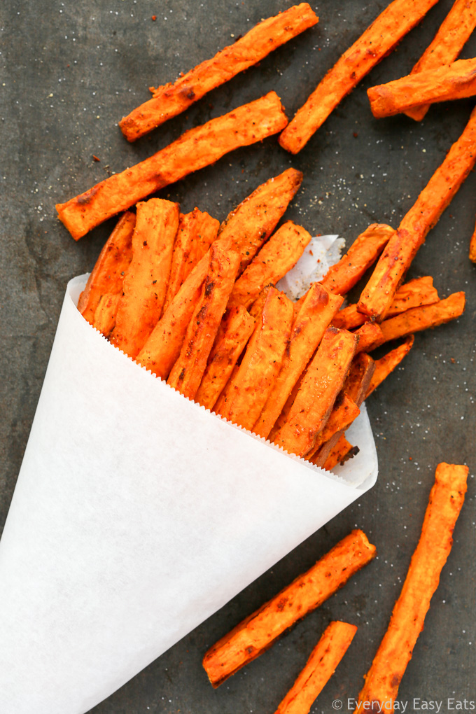 Overhead view of Spicy Baked Sweet Potato Fries on a dark background.