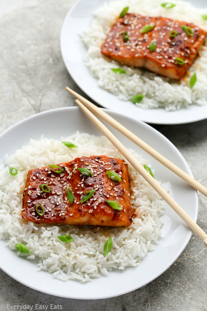 Overhead view of two plates of Honey Sriracha Salmon sitting on a bed of white rice with chopsticks.