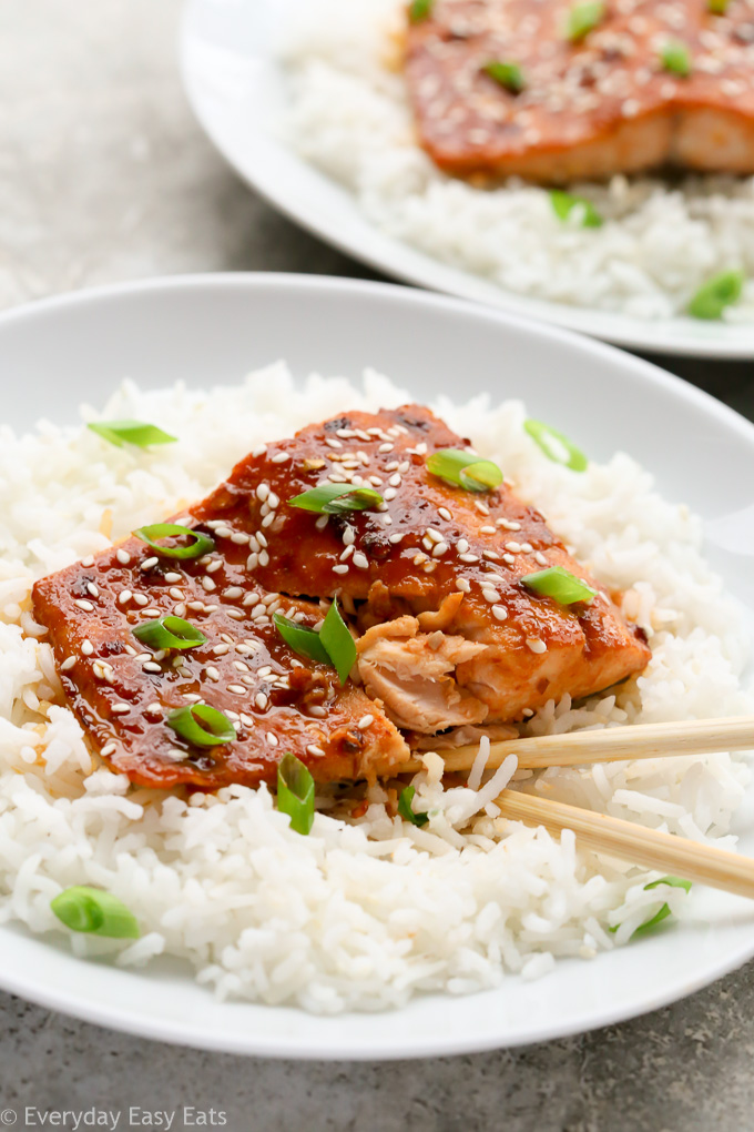 Close-up view of a plate of Honey Sriracha Salmon on a bed of white rice with chopsticks.