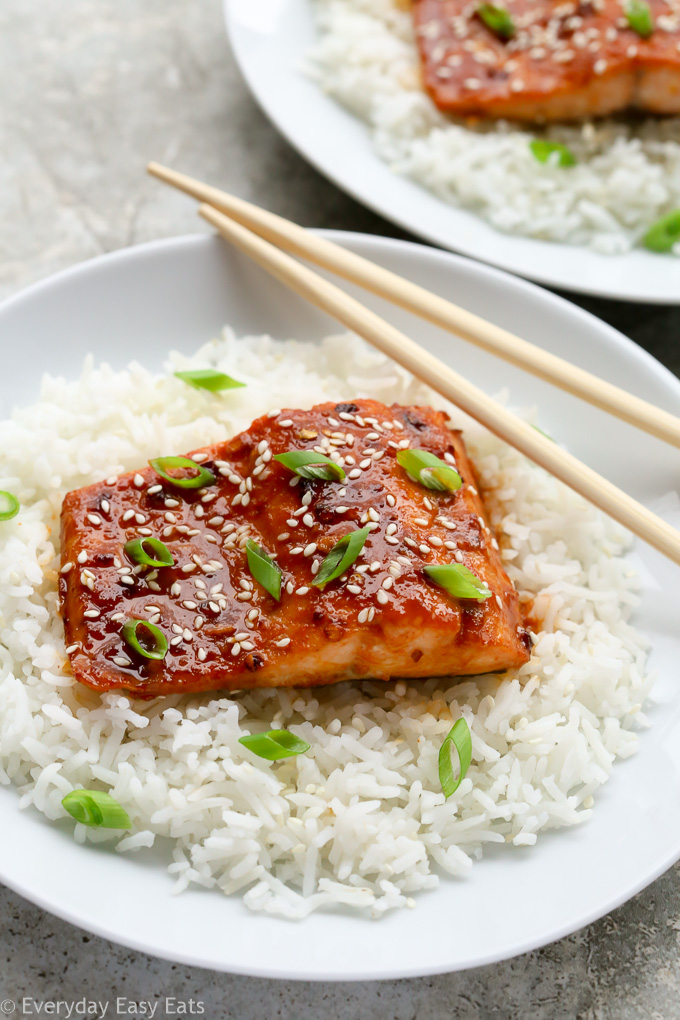 A plate of Honey Sriracha Salmon sitting on a bed of white rice with chopsticks.