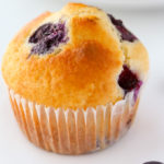 Close-up overhead view of a blueberry muffin on a white background.