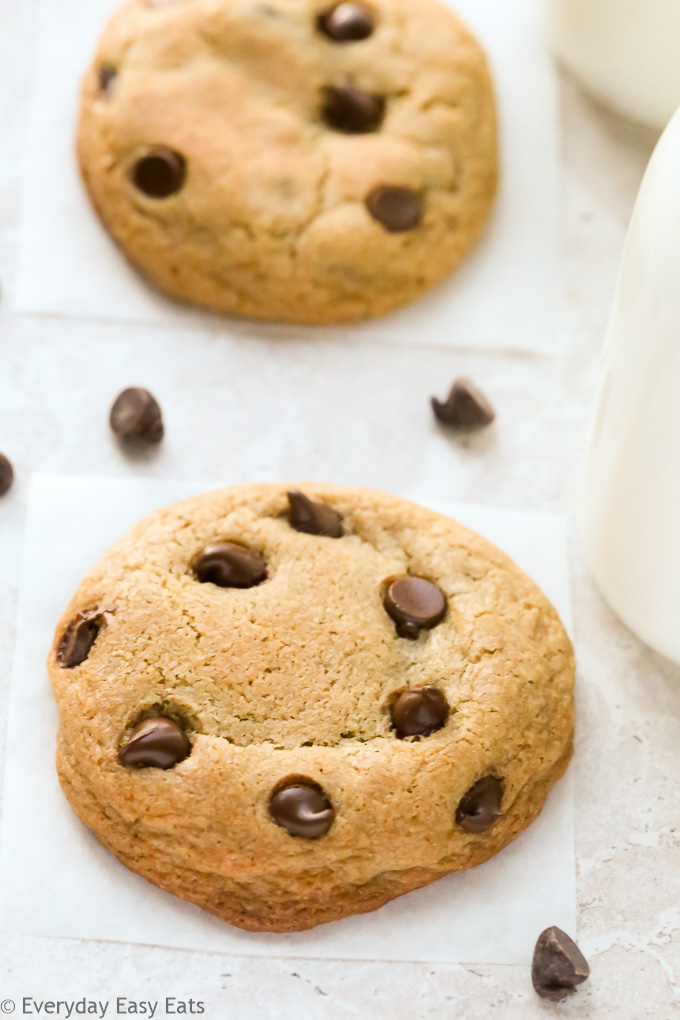 Close-up overhead view of Soft Chewy Chocolate Chip Cookies with scattered chocolate chips on a neutral background.