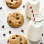 Overhead view of The Best Soft and Chewy Chocolate Chip Cookies with glasses of milk and scattered chocolate chips on a neutral background.