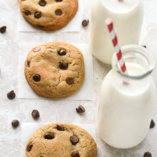 Overhead view of Soft Chewy Chocolate Chip Cookies with glasses of milk and scattered chocolate chips on a neutral background.