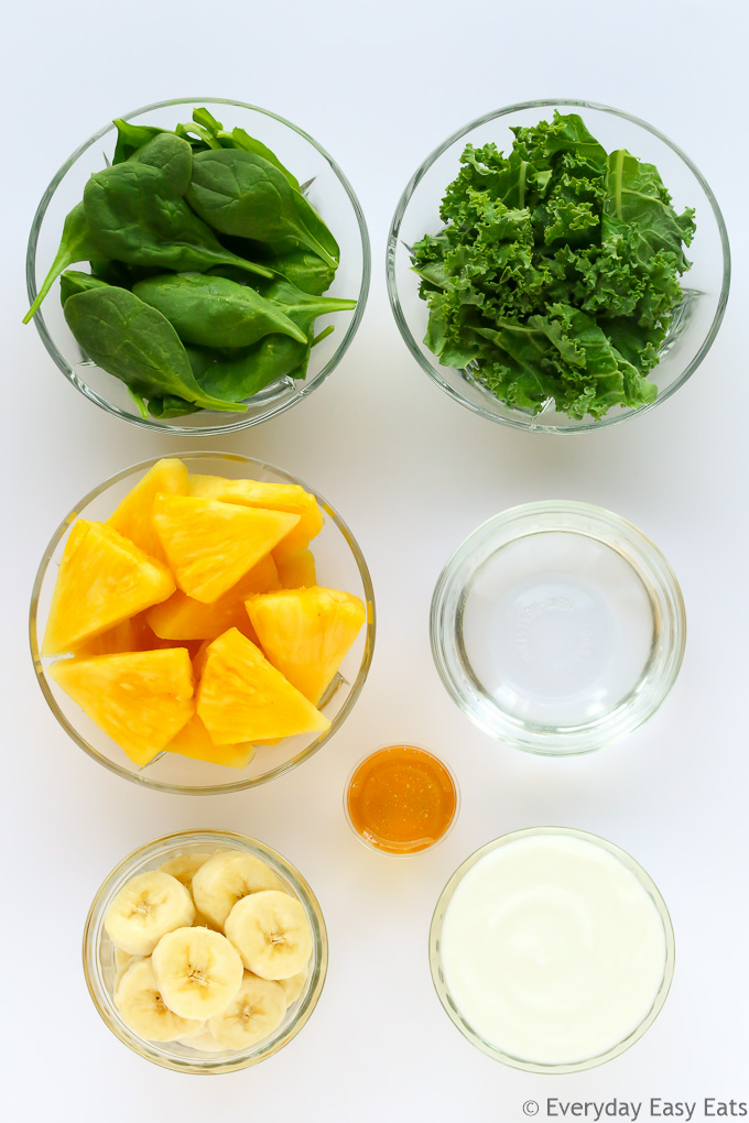 Overhead view of Breakfast Green Smoothie ingredients in glass bowls on a light background.