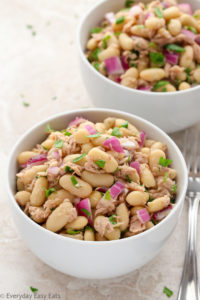 Overhead view of two bowls of Tuna White Bean Salad on a neutral-colored background.