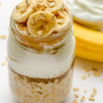 Overhead view of Banana Overnight Oats with Greek Yogurt in a mason jar against a white background.