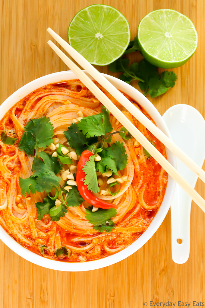 Budget-Friendly Meal: Overhead view of a bowl of Thai Spicy Noodle Soup with chopsticks and a spoon on a wooden background.