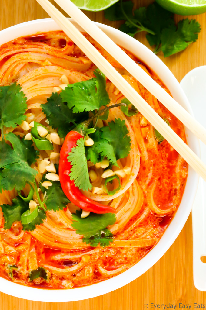 Close-up overhead view of Thai Noodle Soup in a white bowl on a wooden background.