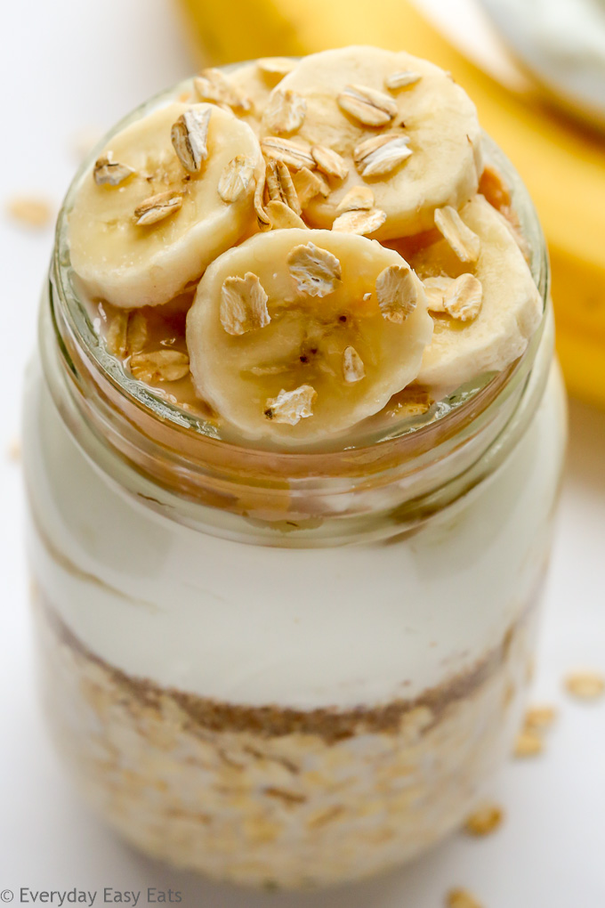 Close-up overhead view of Banana Overnight Oats with Greek Yogurt in a mason jar against a white background.