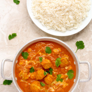 Overhead view of Quick Indian Chicken Curry in a silver serving bowl with a plate of white rice.