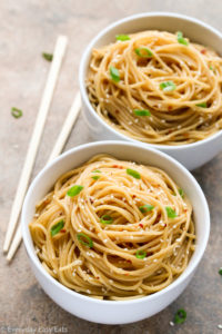 Overhead view of two bowls of Easy Sesame Noodles with chopsticks on the side on a neutral background.