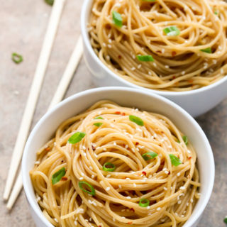 Overhead view of two bowls of Sesame Noodles with chopsticks on the side on a neutral background.