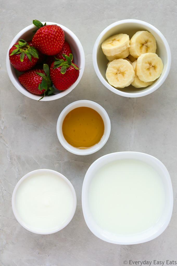Overhead view of Strawberry Banana Smoothie ingredients in white bowls on a light background.