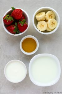 Overhead view of Strawberry Smoothie with Yogurt ingredients in white bowls on a light background.