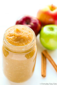 Overhead view of a open jar of Unsweetened Applesauce with apples and cinnamon sticks behind it on a white background.