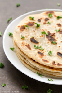 Side view of a stack of Easy Homemade Flatbread (No Yeast) in a white plate on a dark background.