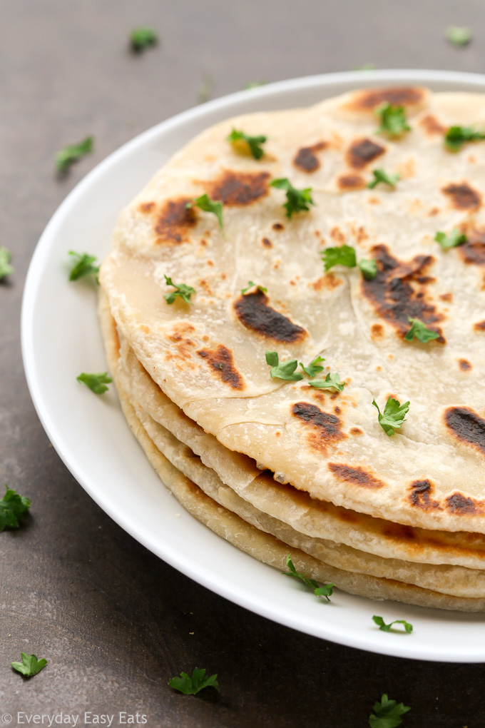Side view of a stack of No-Yeast Flatbread in a white plate on a dark background.