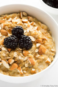 Close-up overhead view of Brown Sugar Oatmeal in a white bowl topped with chopped almonds and blackberries.