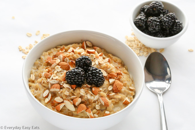 Overhead view of Brown Sugar Oatmeal in a white bowl and spoon on the side, topped with chopped almonds and blackberries.