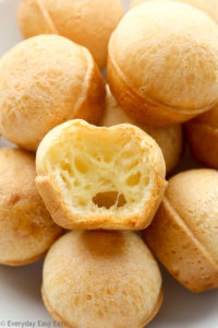 Side view of Brazilian Cheese Bread (Pão de Queijo) in a white plate, one piece has a bite taken out of it.