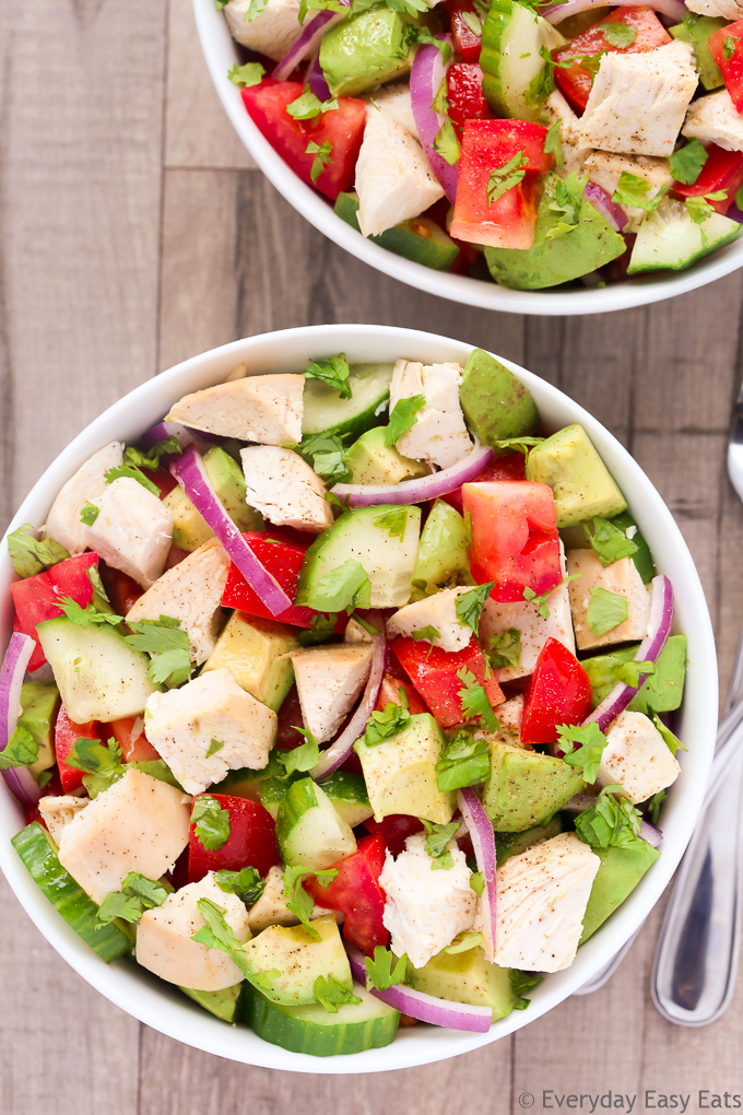 Close-up overhead view of a bowl of Chicken Avocado Salad on a beige background.