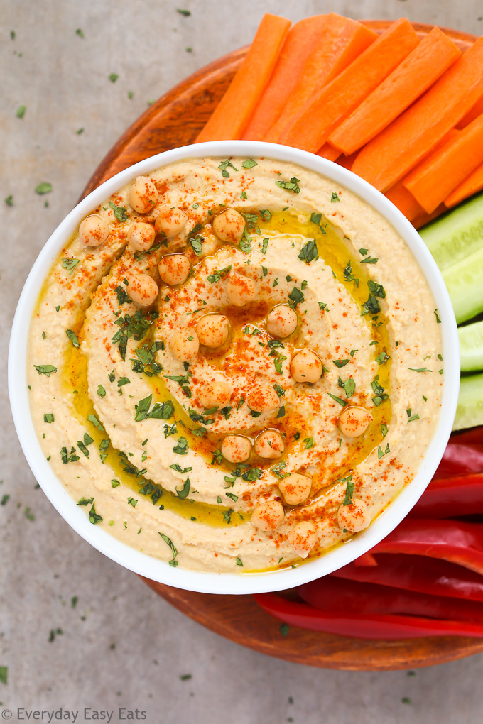 Overhead view of a bowl of Hummus Without Tahini with chopped vegetables on a neutral background.